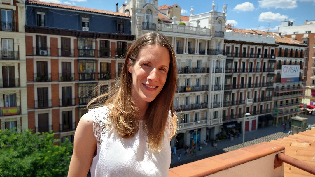Photo of a smiling young woman on a roof terrace with the sun on her face in front of a backdrop of Spanish-style apartments.