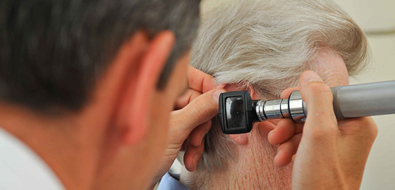 Close-up view of audiologist examining male patient's ear with otoscope.