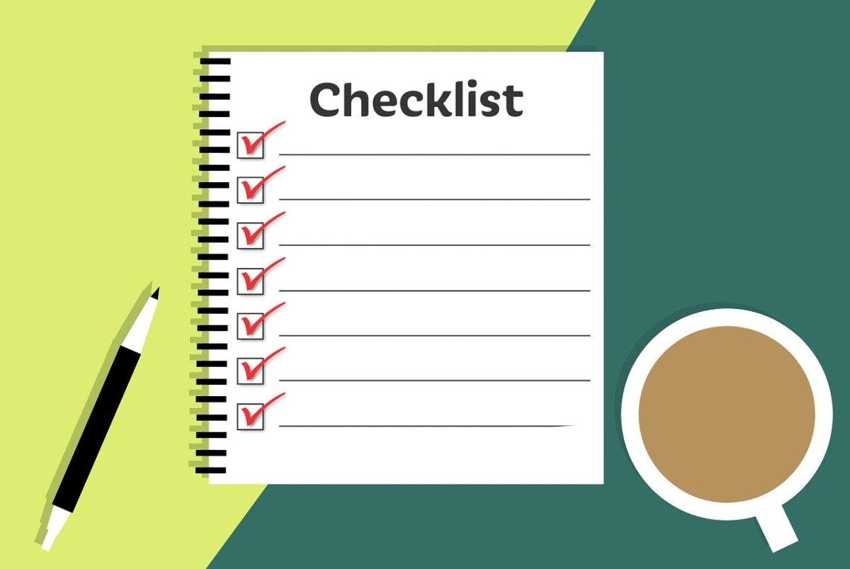 Checklist with ticks in boxes. To the right of the checklist is a cup of tea and to the left is a pen.
