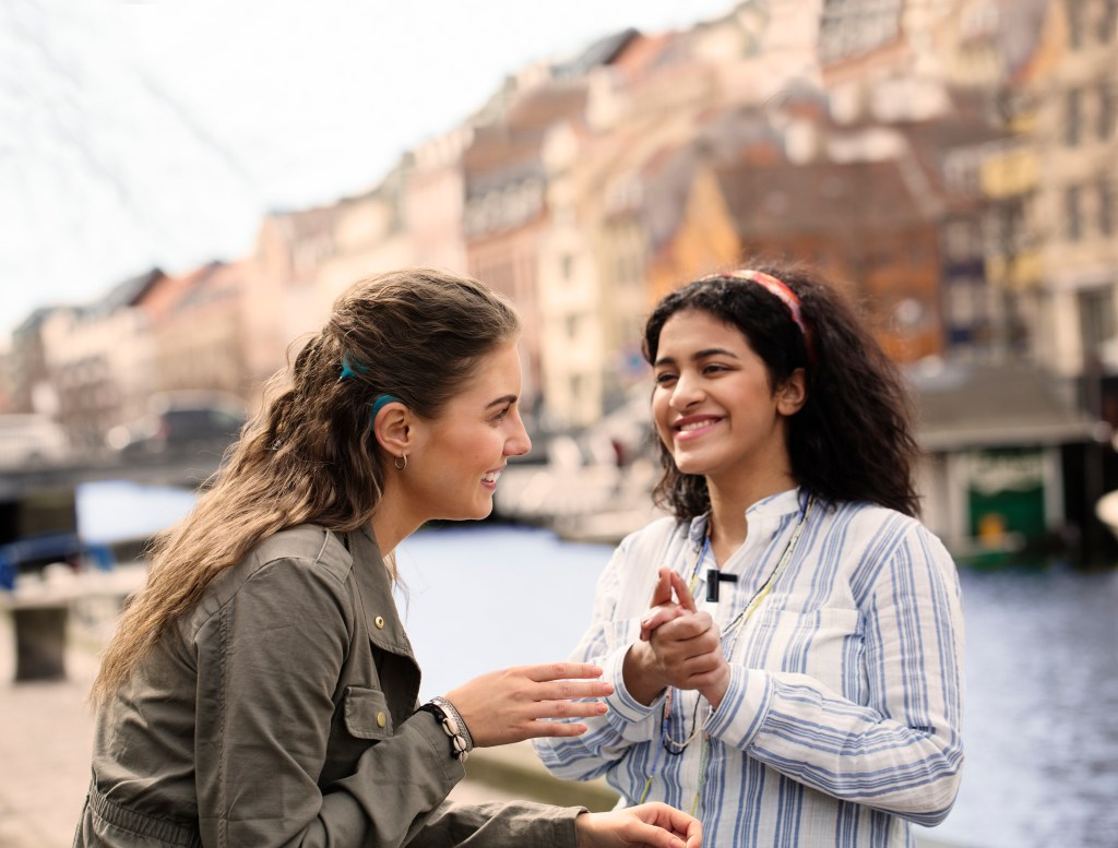 Two woman by a canal. One of the women has a cochlear implant. The women are talking and smiling.