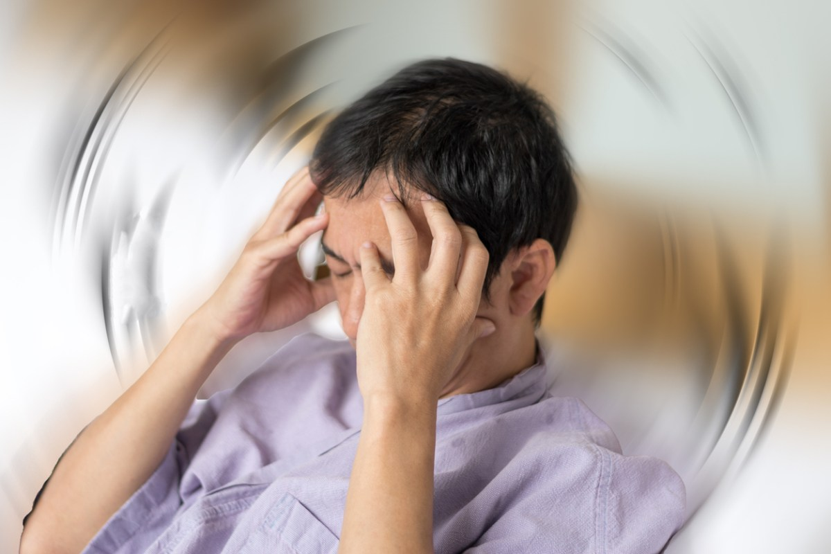 Featured Image Description: Vertigo illness concept. Man with hands on his head and eyes closed, against a spinning background.
