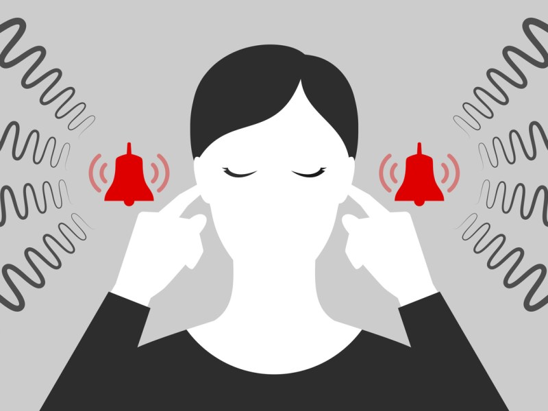 Woman with closed eyes is plugging her ears with fingers when suffering from tinnitus. Red bells as symbol of ringing in ears.