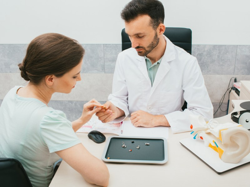 A male audiologist selects a hearing aid for a female patient.