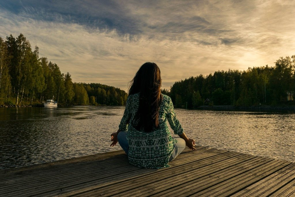 Woman sitting on decking by water in meditation pose.