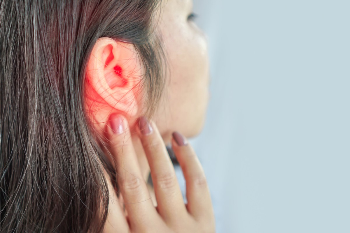 Woman's ear, highlighted in red. Hearing loss concept.