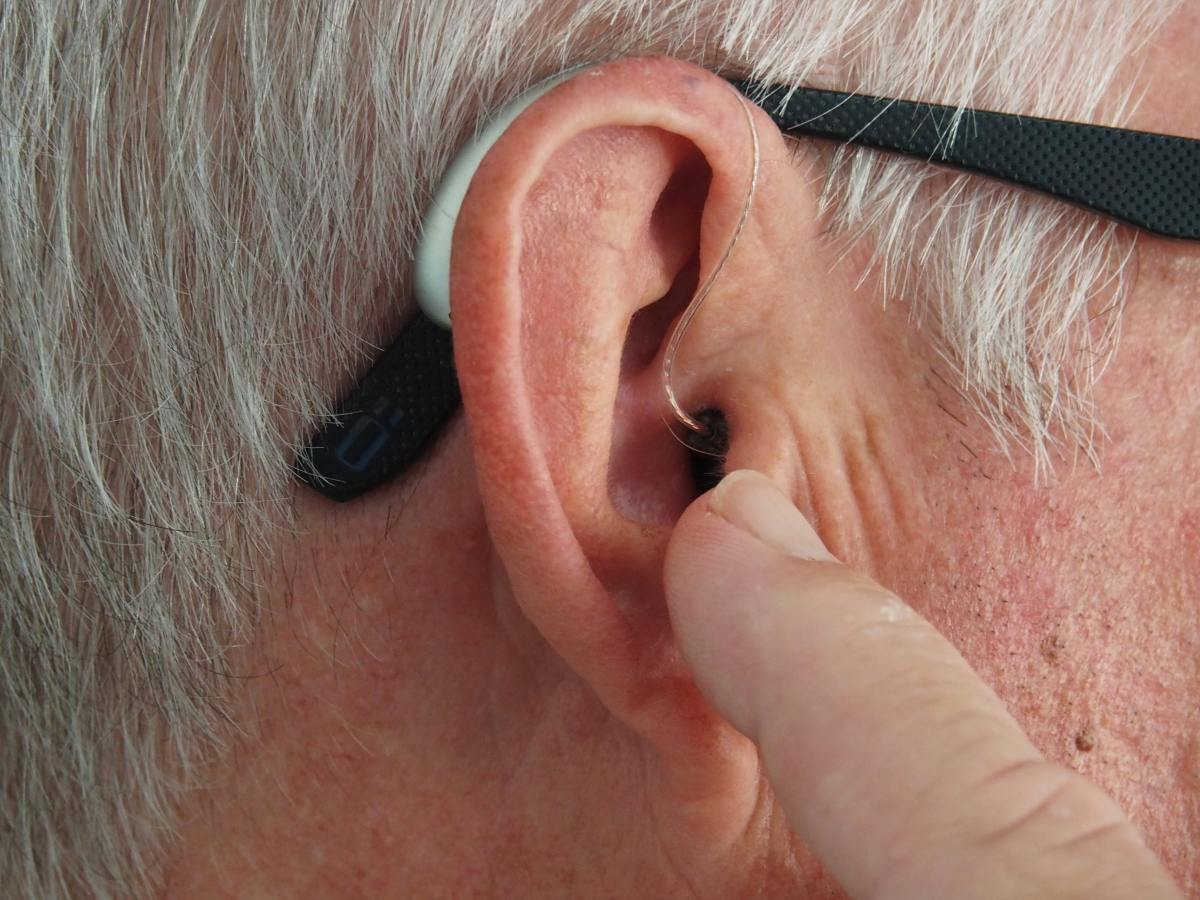 Close up of ear with hearing aid and glasses.